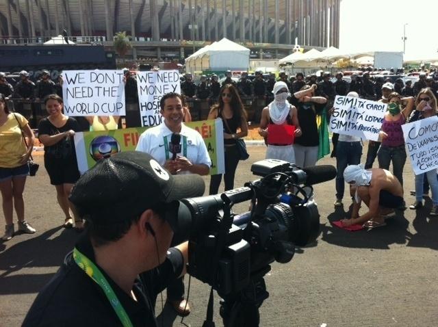 15.jun.2013 - Manifestantes aproveitaram a presença de jornalistas estrangeiros para expor cartazes em inglês com suas reivindicações. Na imagem, uma equipe da UNivision, rede de Tv dos Estados Unidos