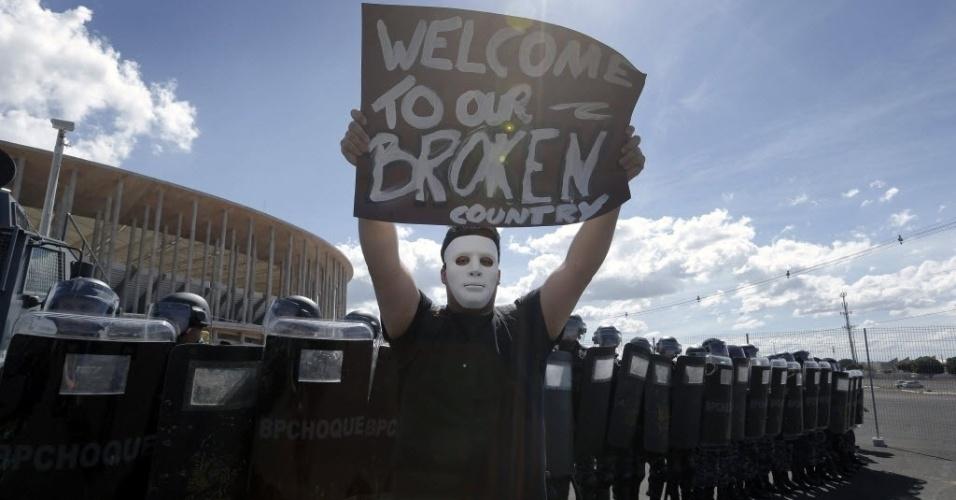 15.jun.2013 - Manifestantes utilizam máscaras e cartazes em inglês durante protesto nos arredores do estádio Mané Garrincha, em Brasília