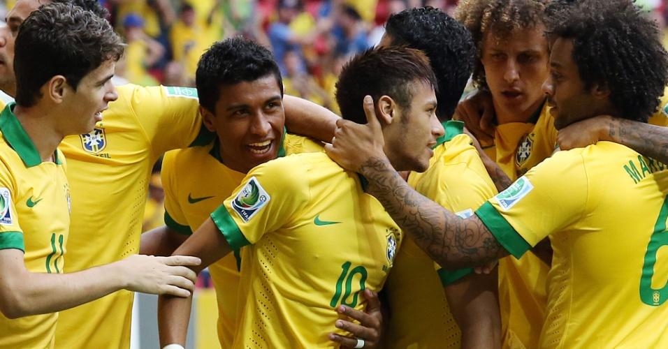 15.jun.2013 - Neymar é abraçado pelos companheiros de seleção brasileira após marcar um belo gol contra o Japão