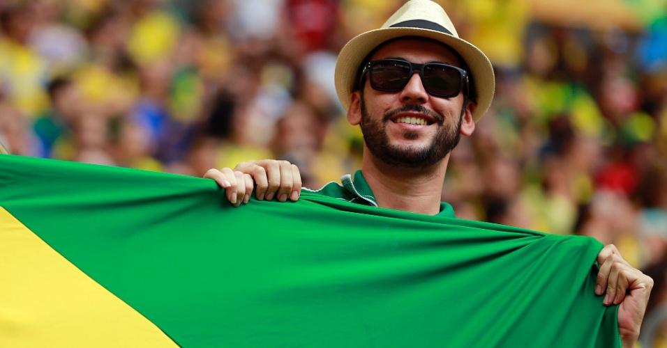 15.jun.2013 - Torcedor estica a bandeira do Brasil na arquibancada do Mané Garrincha antes do jogo do Brasil contra o Japão
