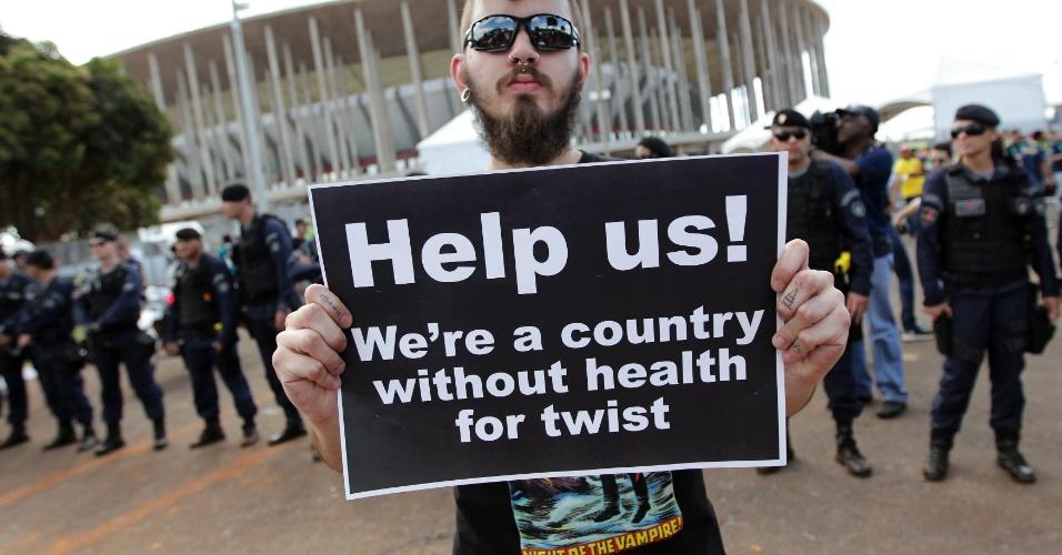 15.junho.2013 - Na porta do estádio, manifestante carrega cartaz em inglês com críticas ao país