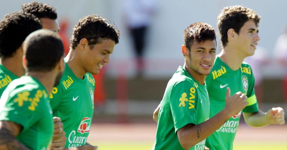 16.jun.2013 - Neymar e Oscar puxam a fila de jogadores durante treino da seleção brasileira em Brasília