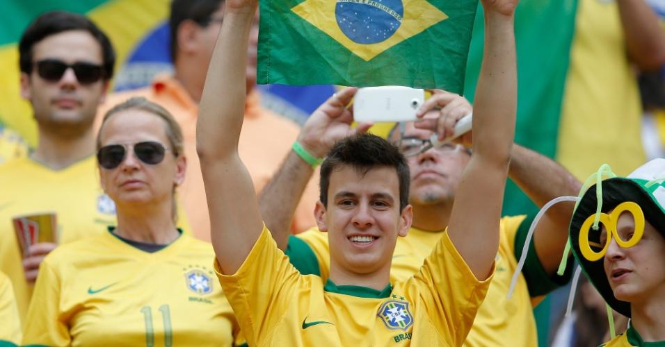 Torcedor brasileiro exibe bandeira na arquibancada do Mané Garrincha em jogo do Brasil contra o Japão