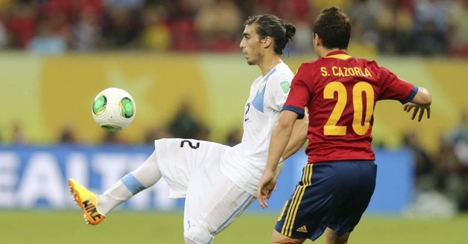18.jun.2013 - O zagueiro da seleção do Uruguai Martín Cáceres tenta controlar a bola diante da marcação de Santi Cazorla, da Espanha, em partida válida pela Copa das Confederações