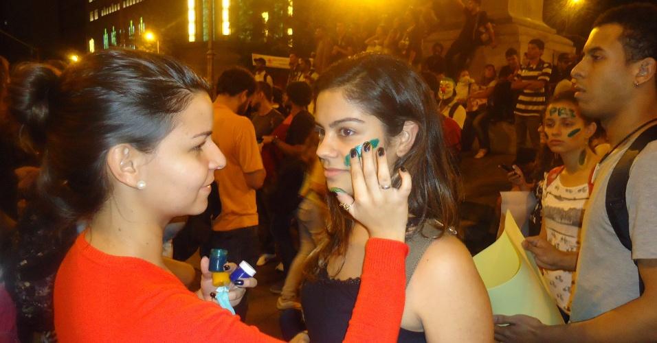 18.jun.2013 - Jovem pinta o rosto de amiga durante protesto em Belo Horizonte. Realização da Copa do Mundo no Brasil foi alvo dos ativistas na capital mineira
