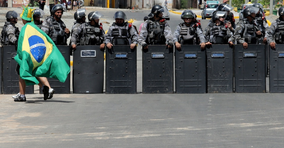 19.jun.2013 - Enrolado em bandeira do Brasil, torcedor se aproxima de barreira policial em frente ao Castelão