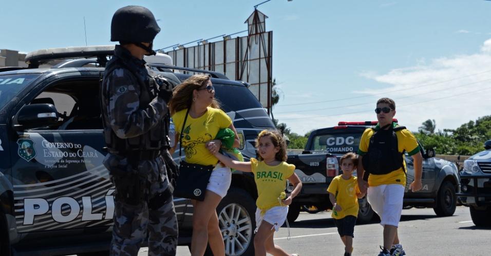 19.jun.2013 - Familias chegam ao estádio Castelão para a partida entre Brasil e México, passando próximas do confronto entre policiais e manifestantes