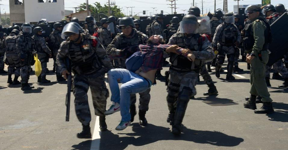19.jun.2013 - Manifestante é arrastado por policiais durante confronto nas imediações do estádio Castelão, em Fortaleza