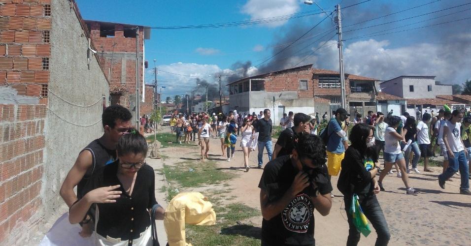 19.jun.2013 - Manifestantes cobrem o rosto para se proteger de fumaça de viatura incendiada e do gás lacrimogênio lançado pela polícia
