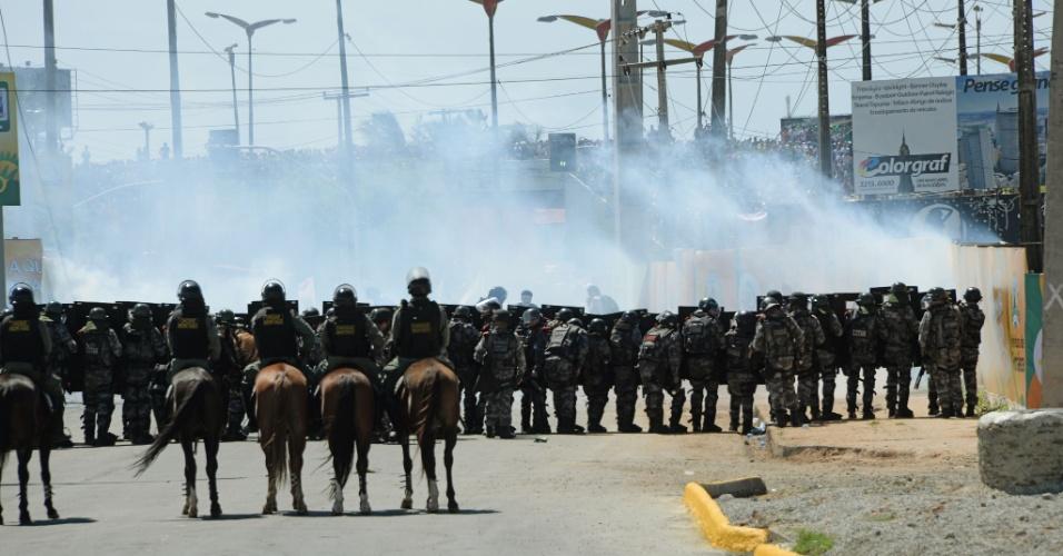 19.jun.2013 - Policiais jogam bombas de gás lacrimogênio para tentar evitar avanço de manifestantes nas imediações do estádio Castelão, em Fortaleza