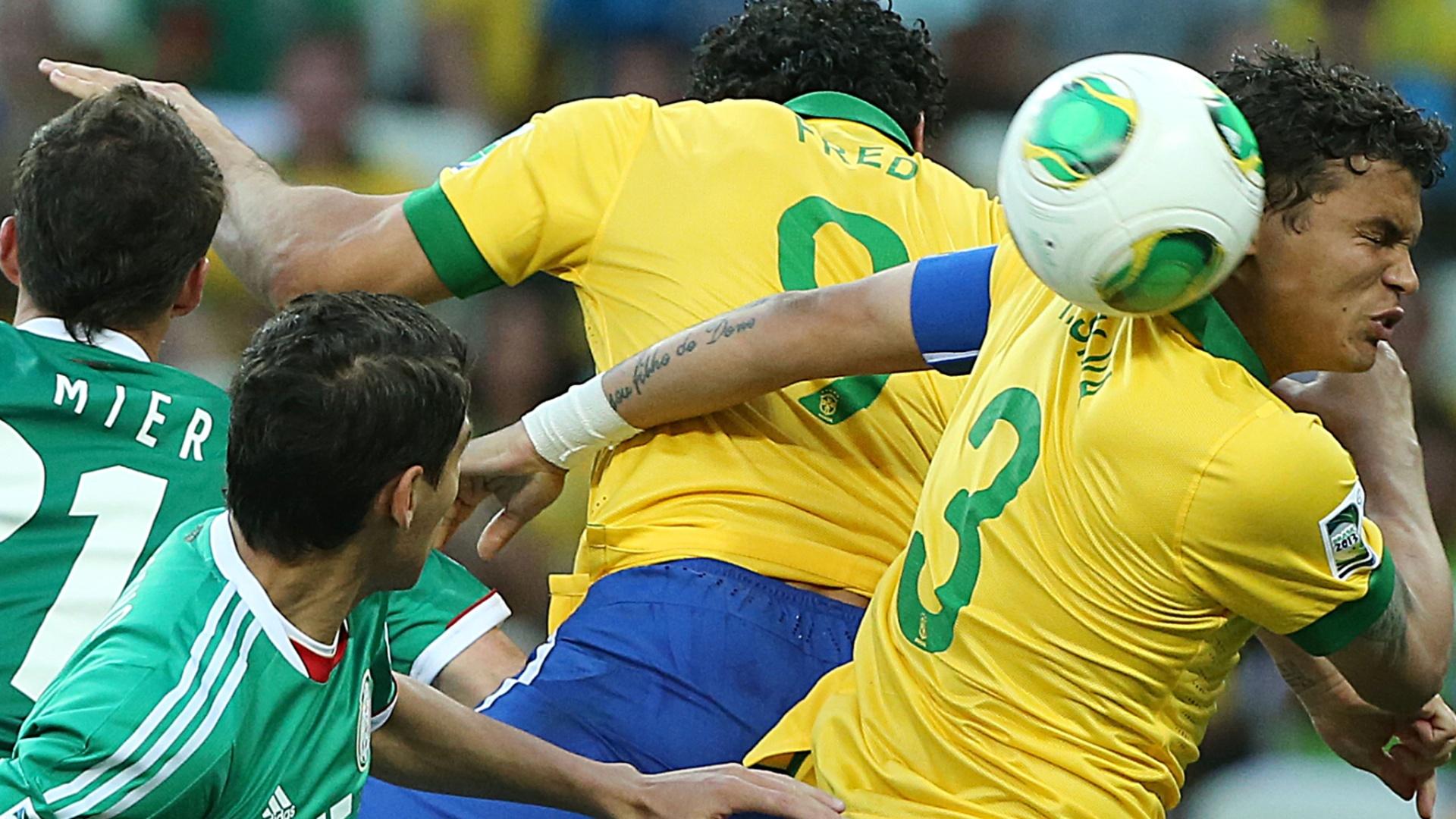 19.jun.2013 - Thiago Silva e Fred sobem para tentar cortar um cruzamento durante a partida entre Brasil e México