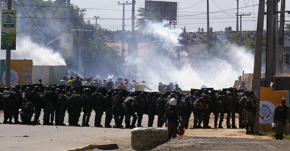 19.junho.2013 - Policiais fazem cordão para impedir que manifestantes cheguem mais perto do estádio