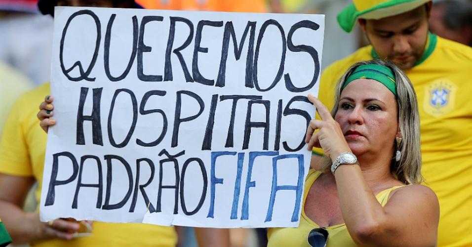 19.junho.2013 - Torcedora se manifesta contra os gastos da Copa dentro do estádio Castelão, em Fortaleza, antes de jogo do Brasil
