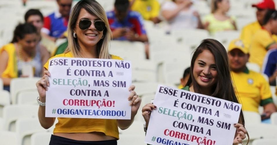 19.junho.2013 - Torcedoras levam ao estádio cartazes protestando contra a corrupção