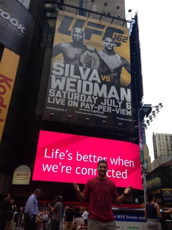 Chris Weidman posa na frente do cartaz de sua luta com Anderson Silva na Time Square, em Nova York