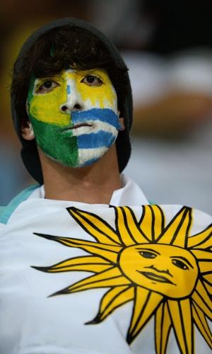 20.jun.2013 - Com rosto pintado nas cores de Brasil e Uruguai, torcedor marca presença na Arena Fonte Nova
