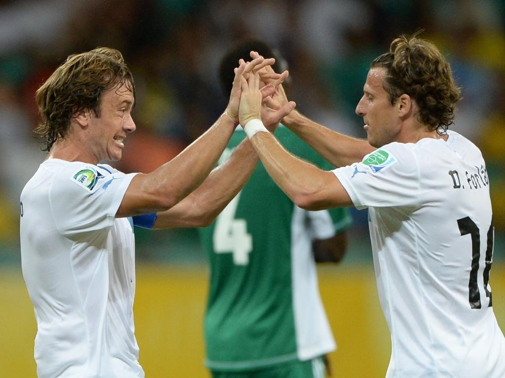 20.jun.2013 - Diego Lugano (e) e Forlán comemoram gol do uruguai sobre a Nigéria na Arena Fonte Nova