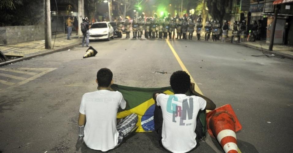 20.jun.2013 - Dois manifestantes sentam na rua em frente a barreira policial durante protesto em Salvador