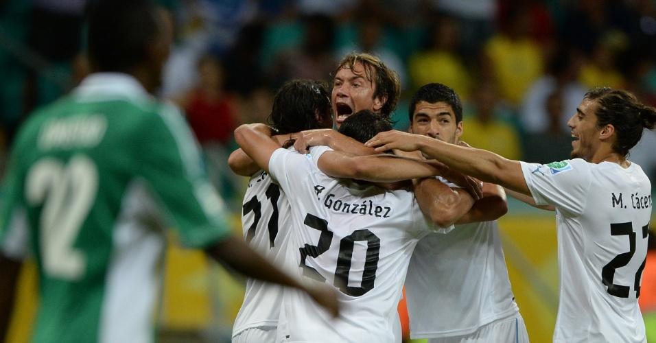 20.jun.2013 - Lugano é abraçado pelos companheiros ao abrir o placar para o Uruguai contra a Nigéria em jogo da Copa das Confederações