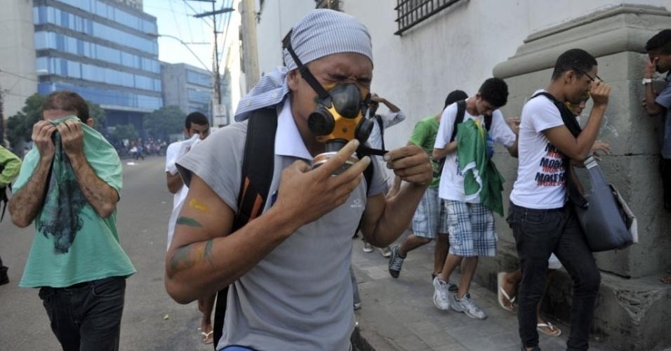20.jun.2013 - Manifestante usa máscara, mas sofre com as bombas de efeito moral jogadas pela polícia no protesto na Arena Fonte Nova, em Salvador