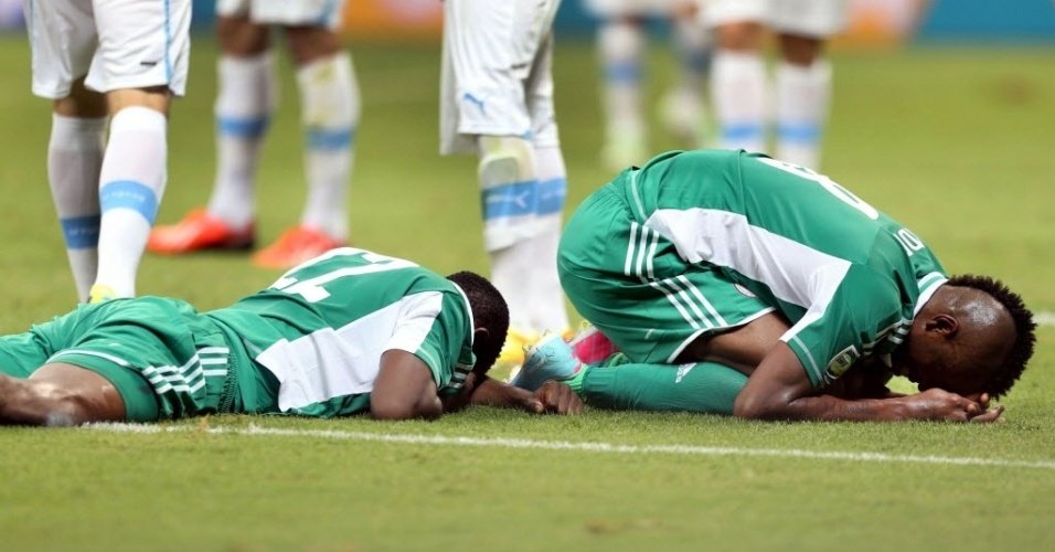 20.jun.2013 - Nigerianos kenneth Omerujo (e) e Brown Ideye lamentam derrota para o Uruguai na Arena Fonte Nova