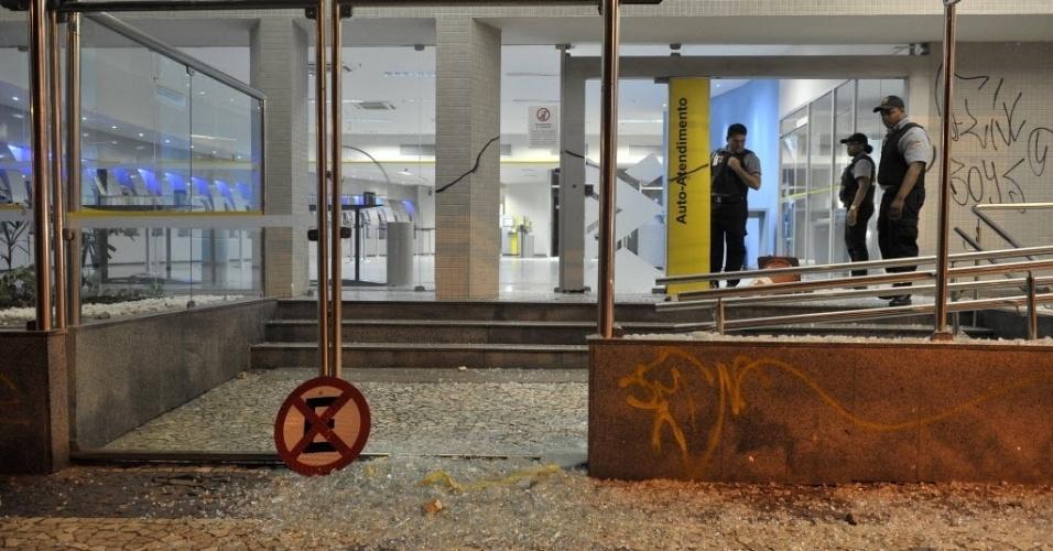 20.jun.2013 - Policiais observam agência bancária que foi depredada por manifestantes durante protesto em Salvador