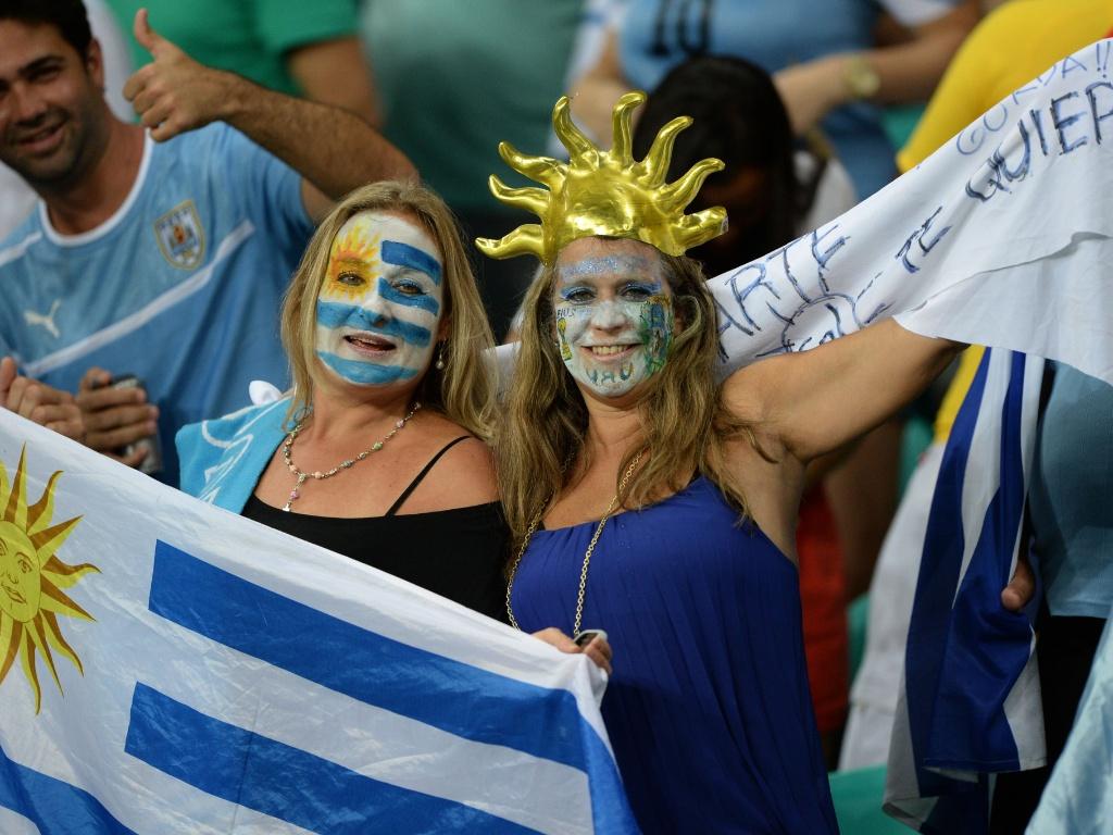 20.jun.2013 - Sorridentes, torcedoras do Uruguai exibem bandeira do país antes de jogo contra a Nigéria