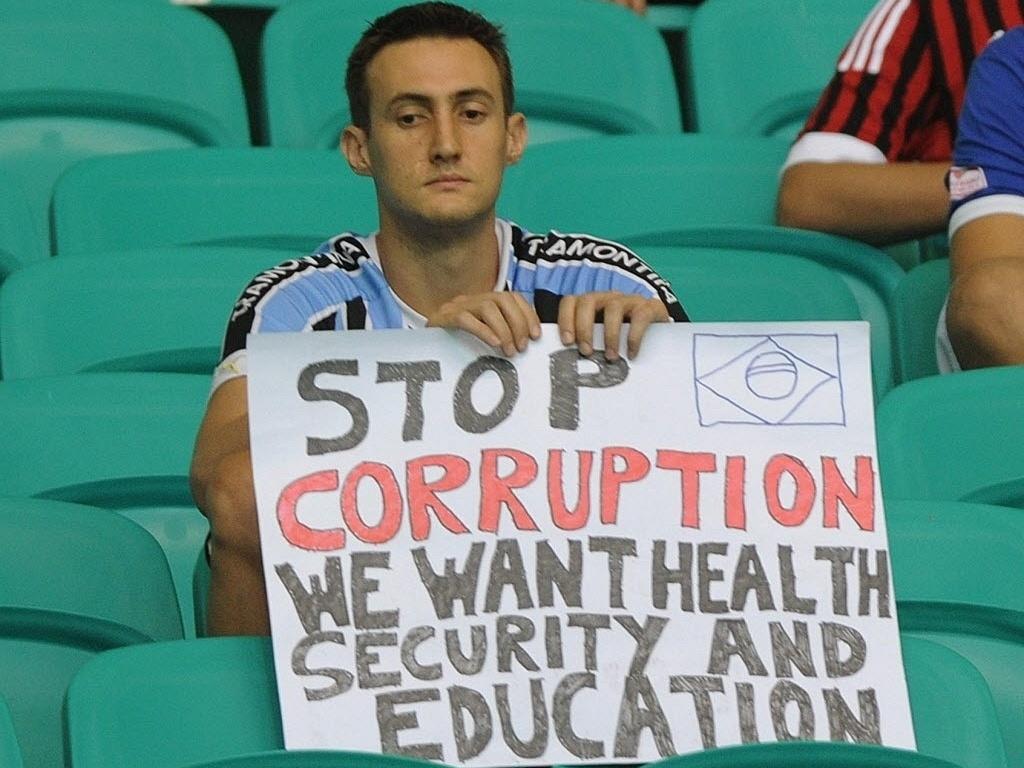 20.jun.2013 - Sozinho na arquibancada da Arena Fonte Nova, torcedor exibe cartaz de protesto durante partida entre Uruguai e Nogéria