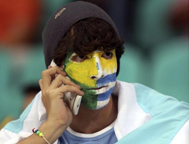 20.jun.2013 - Torcedor fica dividido e pinta rosto com bandeiras de Uruguai e Brasil para assistir ao jogo entre Nigéria e Uruguai