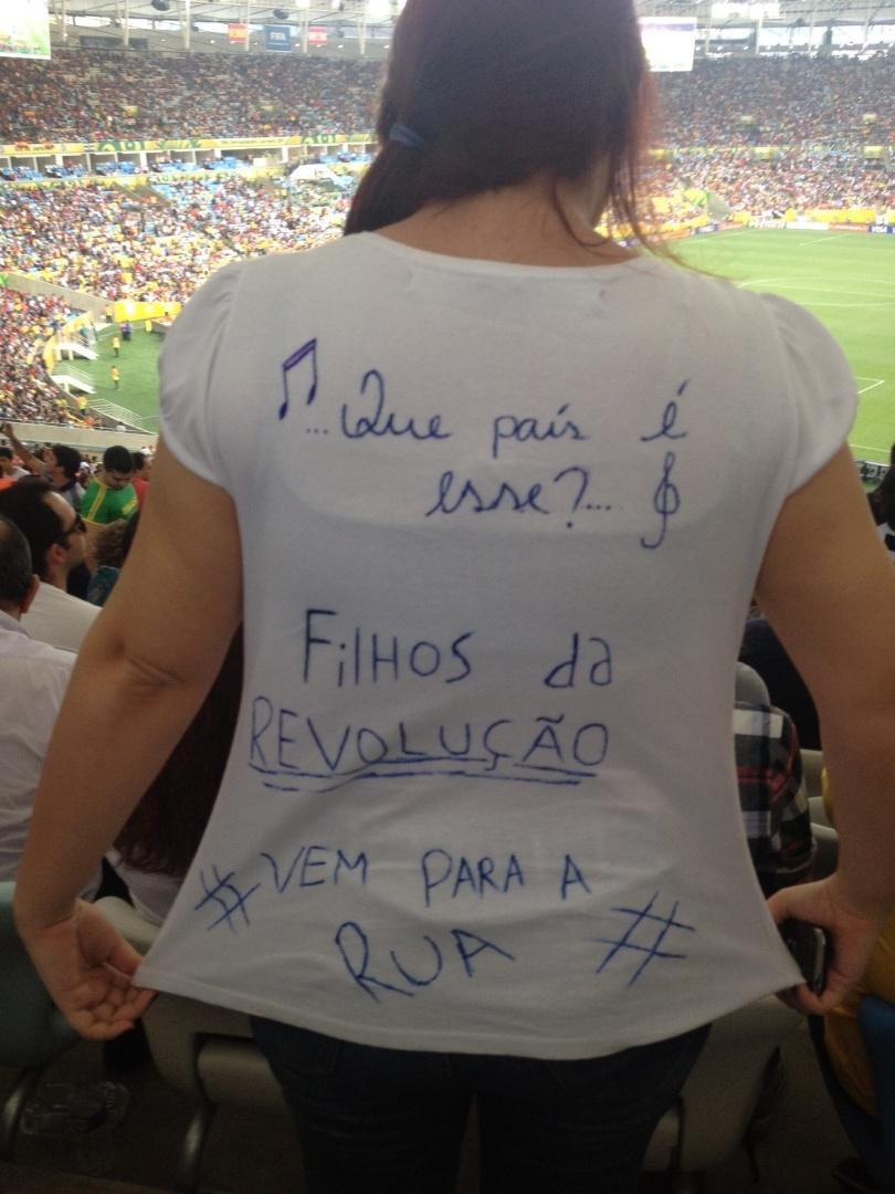 20.jun.2013 - Torcedora escreve em camiseta para protestar nas arquibancadas do Maracanã