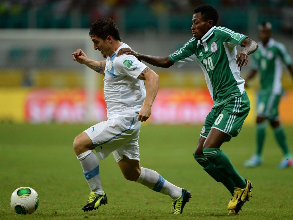 20.jun.2013 - Uruguaio Cristian Rodriguez tenta escapar da marcação de nigeriano Nnamdi Oduamadi durante partida pela Copa das Confederações