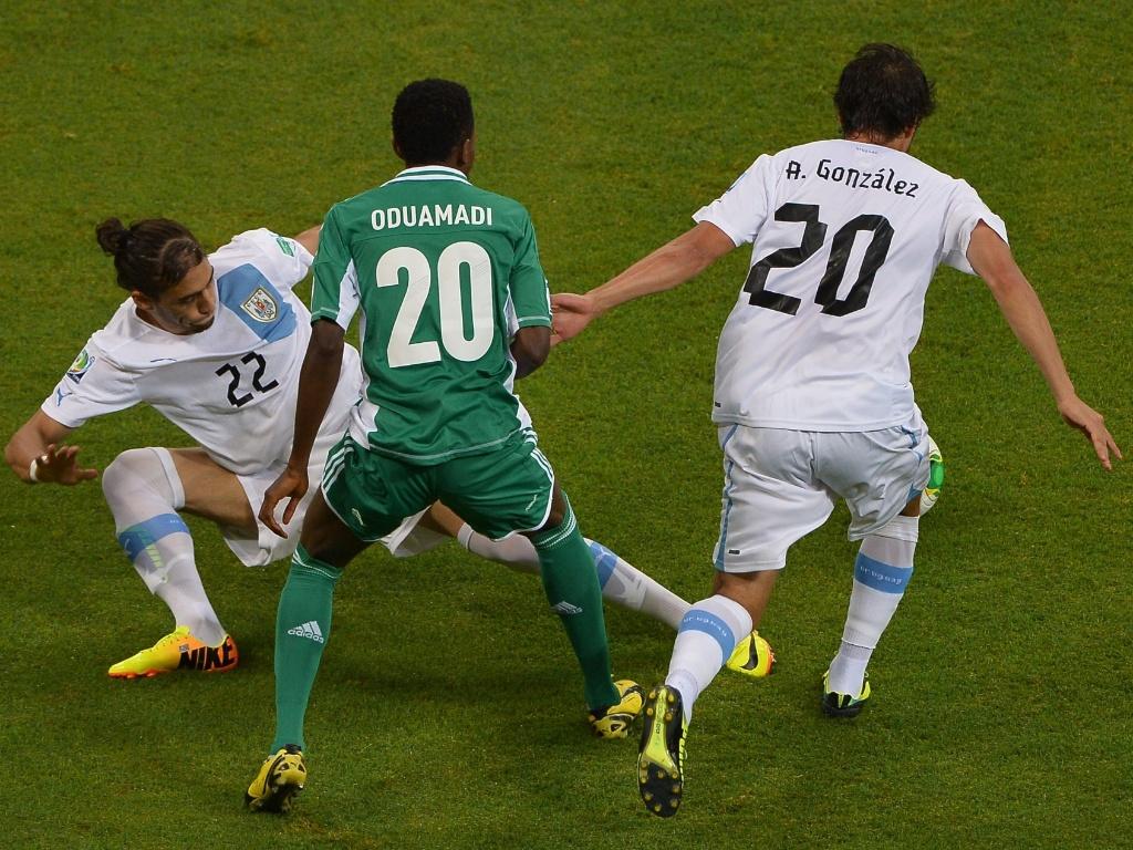 20.jun.2013 - Uruguaios Martin Caceres (e) e Alvaro Gonzalez (d) tentam desarmar nigeriano Nnamdi Oduamadi antes de partida pela Copa das Confederações