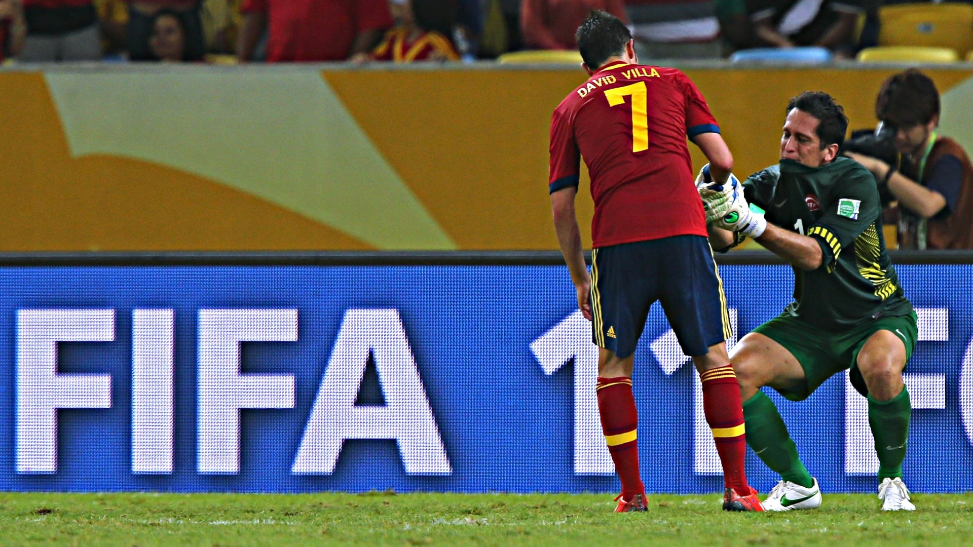 20.junho.2013 - David Villa levanta goleiro do Taiti que, emocionado, caiu no choro após o jogo contra a Espanha