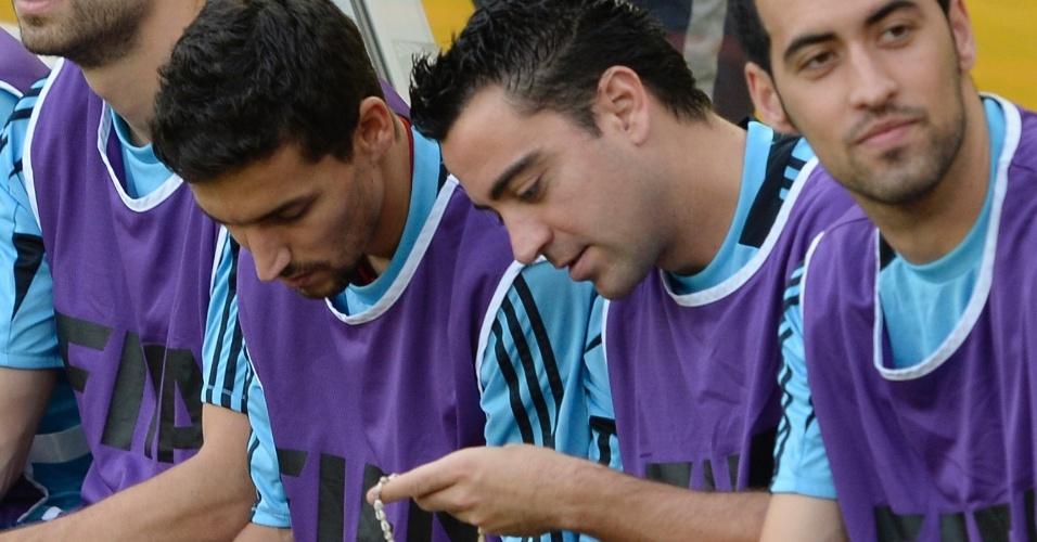 20.junho.2013 - Estrelas da Espanha no banco de reservas contra o Taiti; jogadores brincam com pulseiras oferecidas pelos adversários