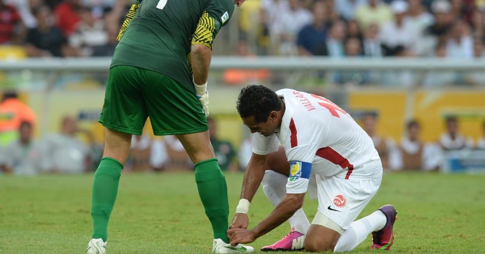 20.junho.2013 - Jogador do Taiti ajuda seu goleiro a amarrar o cadarço da chuteira