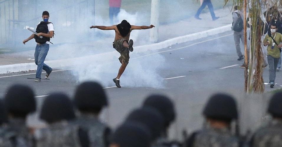 22.06.13 - Manifestante tenta chutar bomba de gás lacrimogênio lançado pelos policiais em Belo Horizonte; conflito com Força Nacional teve feridos dos dois lados
