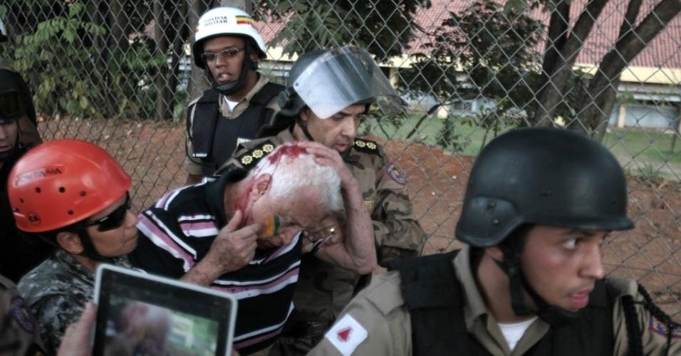 22.06.13 - Policiais ajudam senhor ferido após confronto com manifestantes em Belo Horizonte; conflito com Força Nacional teve feridos dos dois lados