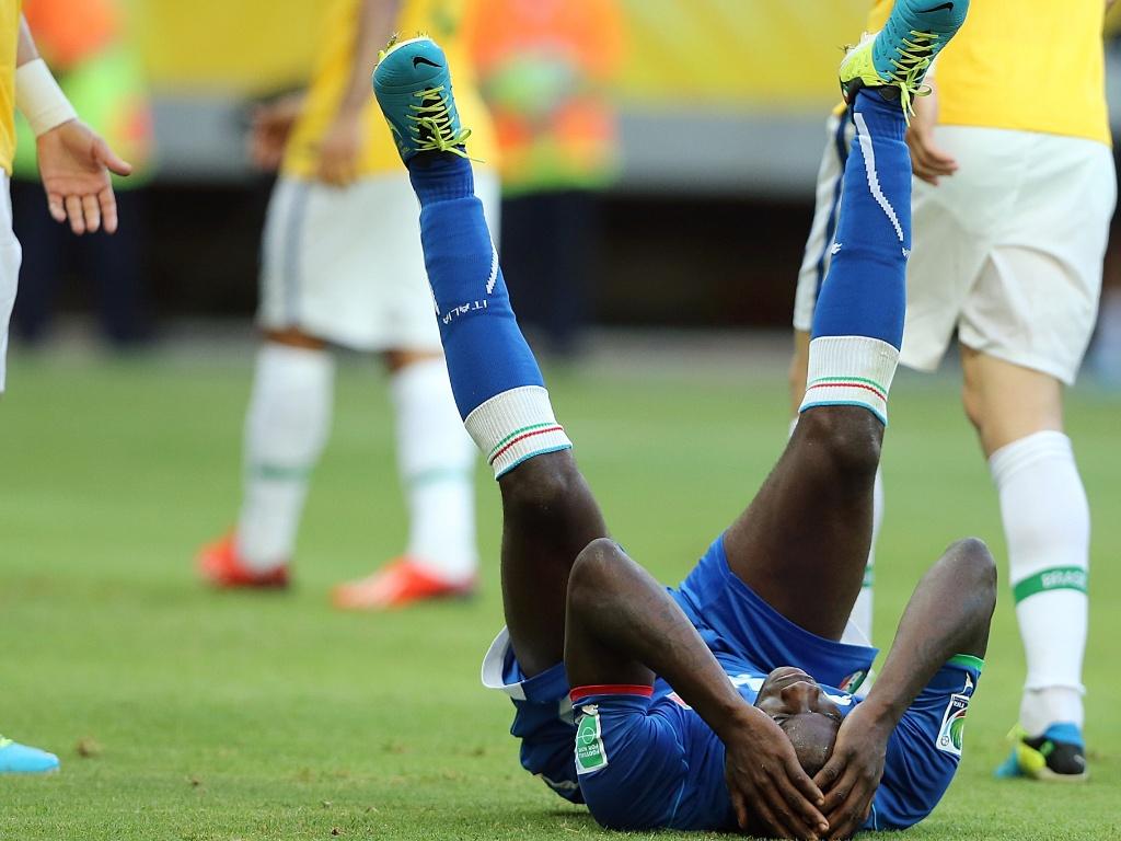 22.jun.2013 - Balotelli cai no chão após sofrer falta na partida entre Brasil e Itália