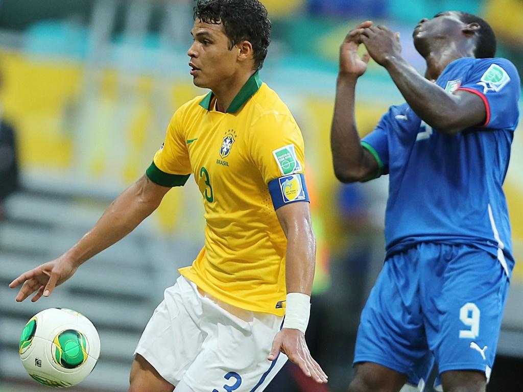 22.jun.2013 - Thiago Silva protege a bola em disputa com Balotelli durante jogo entre Brasil e Itália