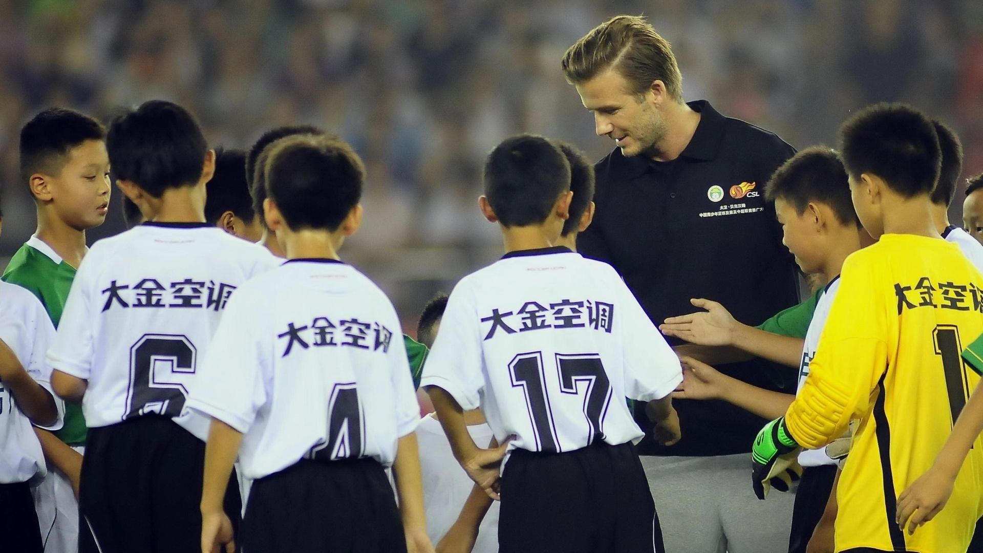 Inglês David Bekcham brincou com crianças chinesas neste sábado, durante jogo da liga chinesa em Hangzhou
