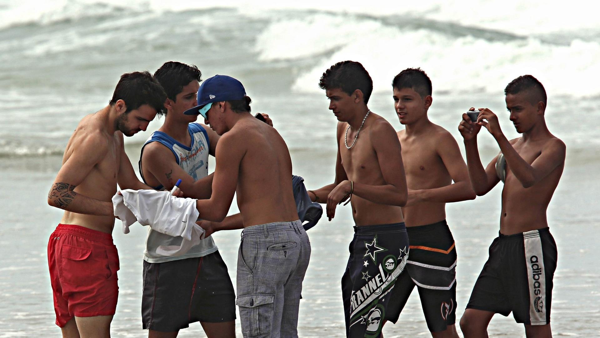 24.jun.2013 - Garotos aproveitam presença de Fàbregas na praia para pedir autógrafo