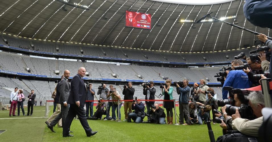 24.jun.2013 - Vários jornalistas e fotógrafos acompanham Josep Guardiola no gramado do Allianz Arena