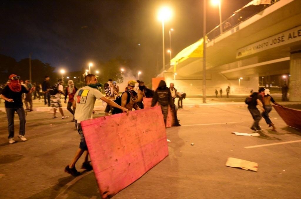 26.jun.2013 - Manifestantes pegam pedaços de madeira para se proteger de balas de borracha da polícia em BH