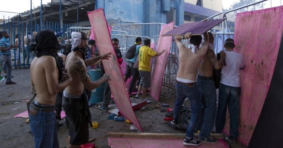 26.jun.2013 - Manifestantes usaram placas de madeira para se proteger de balas de borracha e de bombas de efeito moral lançados pela polícia em confronto próximo ao Mineirão