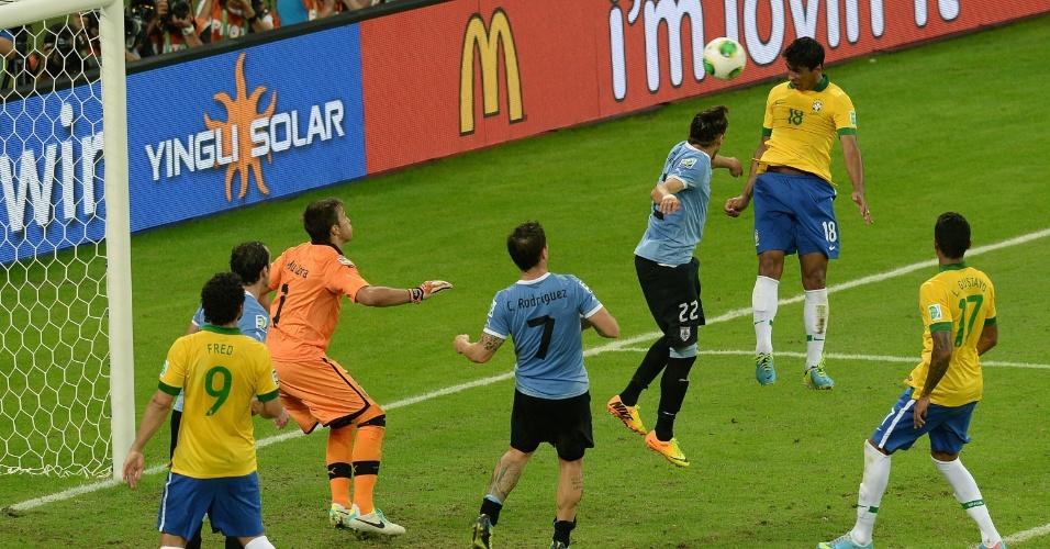 26.jun.2013 - Paulinho sobe mais do que a zaga uruguaia e, de cabeça, marca o gol da vitória brasileira no Mineirão