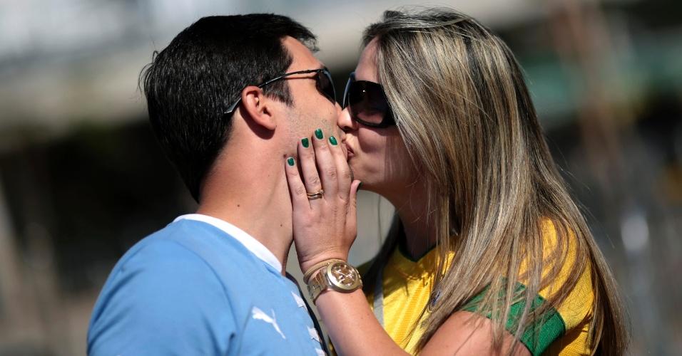 26.jun.2013 - Torcedores esquecem a rivalidade entre Uruguai e Brasil e se beijam antes da semifinal no Mineirão