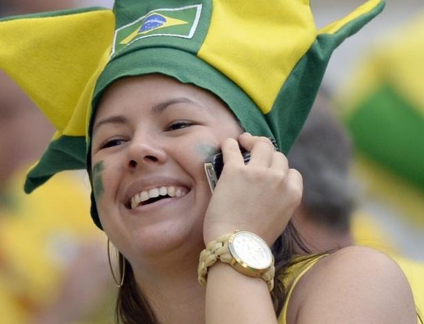 Torcedora do Brasil fala ao celular momentos antes do início da semifinal da Copa das Confederações contra o Uruguai