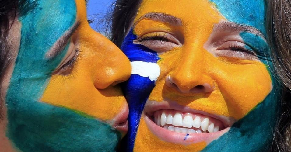 Torcedores pintam o rosto para a partida entre Uruguai e Brasil