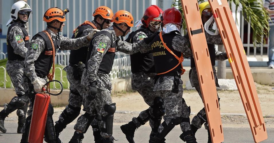 27.jun.2013 - Membros da Força Nacional improvisam macas de emergência como escudos para se protegerem de bombas e pedras atiradas por manifestantes que seguem rumo ao Castelão