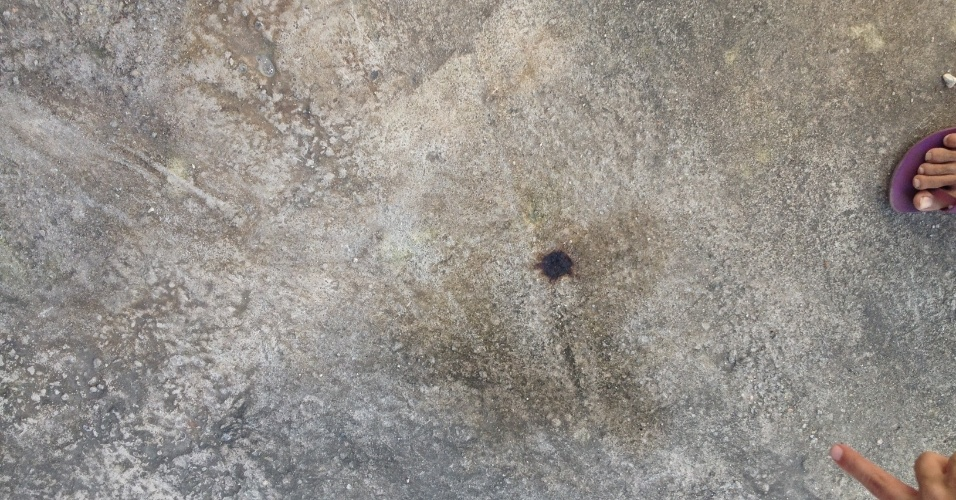 27.06.13 - Marcas no chão do condomínio são mostradas por seus moradores após ação da polícia